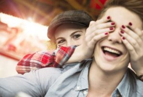 Teenage girl covering eyes of her boyfriend with her hands